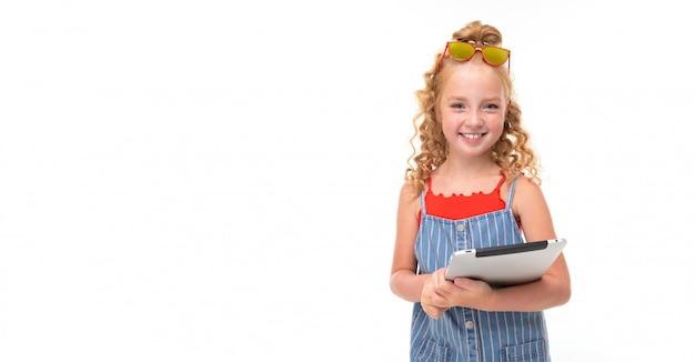Маленькая девочка с рыжими ворсовыми волосами в красном свитере и сине-белый комбинезон в полоску держит планшет. и улыбается.