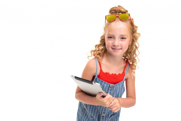 Маленькая девочка с рыжими ворсовыми волосами в красном свитере и сине-белый комбинезон в полоску держит планшет.