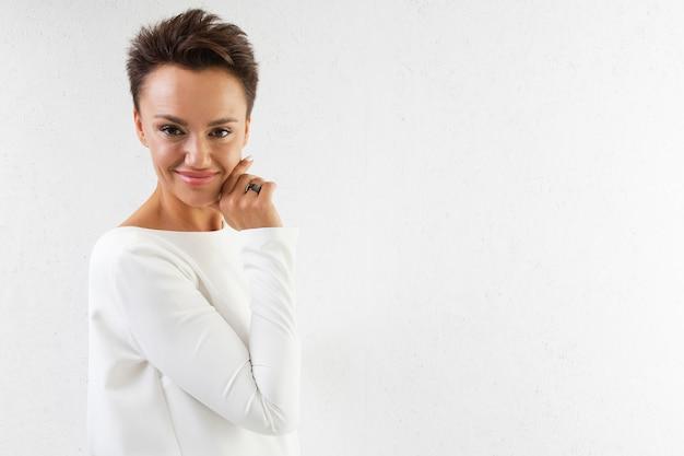 Молодая красивая девушка с короткими темными волосами, макияж, в длинном белом платье с открытой спиной, в розовых лодочках стоит спиной к белой стене