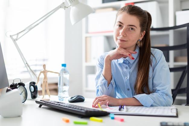 Молодая девушка в офисе сидит за столом компьютера.