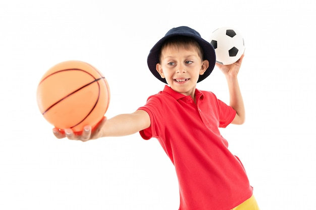 Маленький мальчик в панаме, желтой майке, красных шортах и белых кроссовках стоит с баскетбольными и футбольными мячами