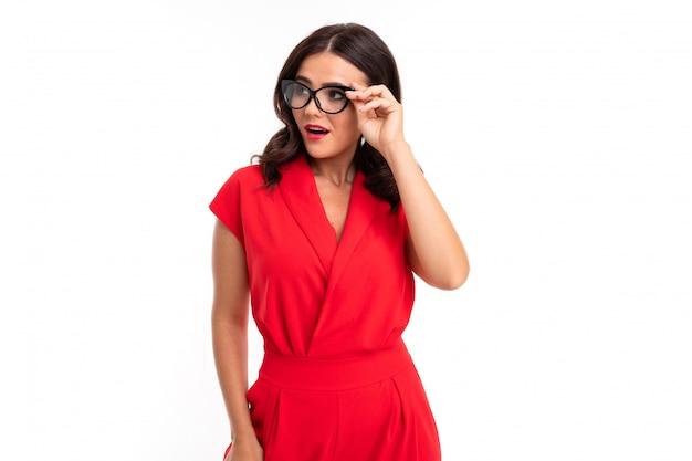 赤い唇、明るい化粧、暗いウェーブのかかった長い髪、赤いスーツの若い女性、透明なスタックの黒い眼鏡が立っています