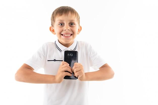 歯と笑みを浮かべて彼の手に携帯電話を持つ幸せな少年、孤立した白地に子供の写真