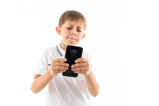 白いシャツの小さな男の子、ブロンドの髪の青いショートパンツ、電話で黒いメガネ