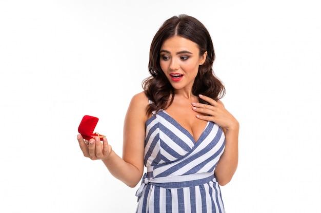 Молодая девушка с восхитительной улыбкой, плоскими зубами, красной помадой, длинными волнистыми каштановыми волосами, красивым макияжем, в бело-голубом платье в полоску с расщеплением, держит в руках красную коробочку с кольцом