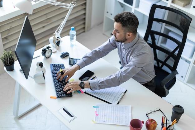 事務所の若い男がテーブルに座り、マーカーを手に持って文書とコンピューターを操作します。