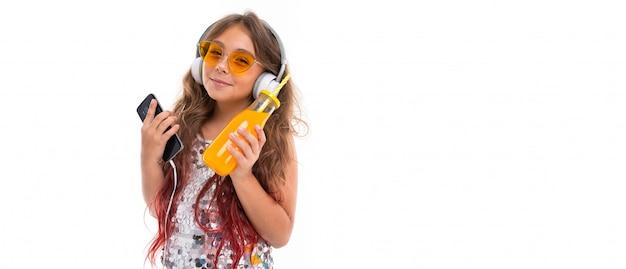 Маленькая девочка с удовольствием слушает музыку и пьет сок