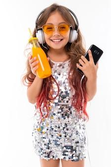 Маленькая девочка в наушниках и апельсиновый сок, слушать музыку