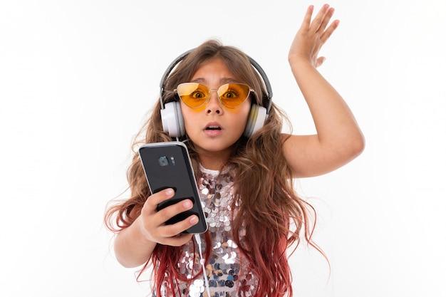 Маленькая девочка в наушниках и оранжевых очках выражает удивление