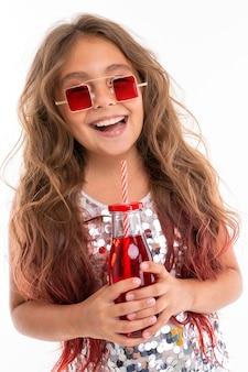 ヒントピンクで染められた長いブロンドの髪を持つ十代の少女、光沢のある明るいドレス、黒と白のスニーカー、メガネ、ヘッドフォンで立って、ストライプのチューブが付いたガラス瓶にジュースを手で押し