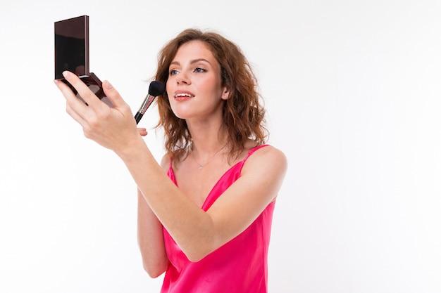 スタイリッシュな女の子は、孤立した白地に化粧を置き、彼女の手に鏡を持っています