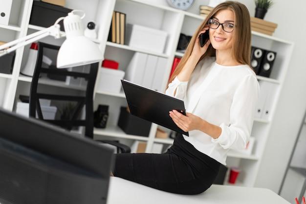 Молодая девушка села на стол в офисе, держа в руке планшет с простынями и разговаривая по телефону.