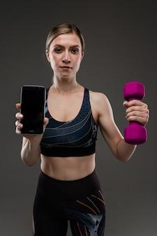 Молодая спортивная девушка с длинными светлыми волосами, набитыми в хвост, красивой внешностью, спортивным телом, в черном топе и бобинах, держит в руках фиолетовые резиновые гантели и телефон