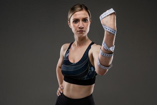 Молодая спортивная девушка с длинными светлыми волосами, набитыми в хвост, красивой внешностью, спортивным телом, в черном топе и бобинах, намотала на руку ленту дюйма
