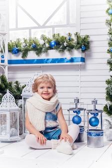 クリスマスツリーの横に座っている少し笑顔のかわいい女の子