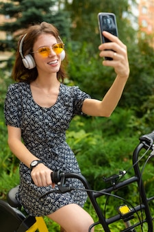 Молодая кавказская женщина с идеальной улыбкой, пухлыми губами, очками, наушниками, гуляет на природе, катается на велосипеде и записывает видео, делает селфи