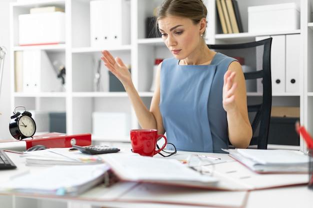 若い女の子が彼女のオフィスのテーブルに座り、両脇に腕を広げた。