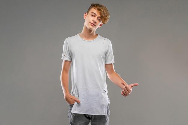 Красивый эмоциональный подросток мальчик позирует в студии на сером, молодой человек в легкой футболке указывает на себя