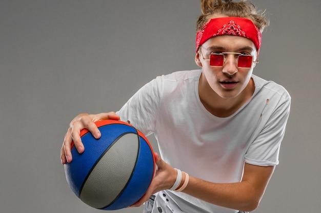 Прохладный молодой человек на сером фоне с мячом в руках, половина выстрел подростка в легкой футболке