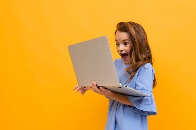ノートパソコンの画面で嬉しそうに叫ぶ少女