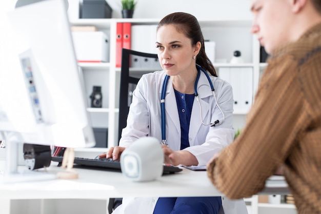 医者はコンピュータ上で患者に問題を説明します。