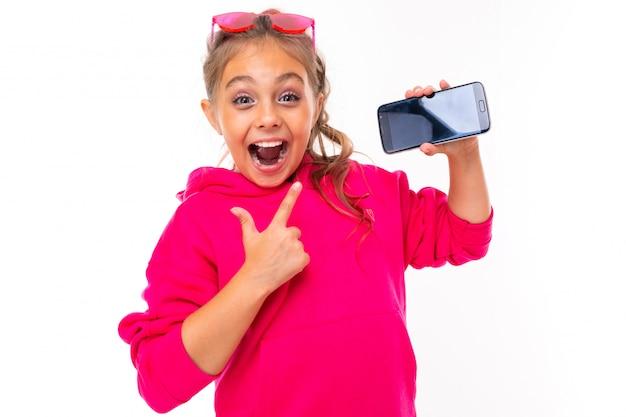 Непослушная девушка в розовой толстовке на белом фоне жестами показывает смартфон
