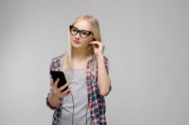 十代の少女は、ヘッドフォンを介して携帯電話から音楽を聴きます。