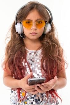 分離された黒のスマートフォンを保持している大きなイヤホンで、黄色のサングラスで深刻な女の子