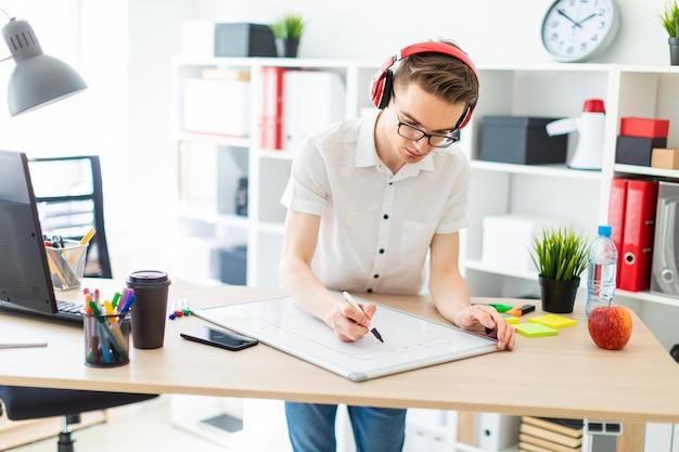 メガネとヘッドフォンを持つ若い男は、磁気ボード上にマーカーを描画します。
