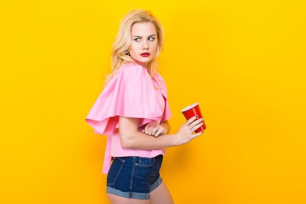 赤いカップとピンクのブラウスに金髪の女性