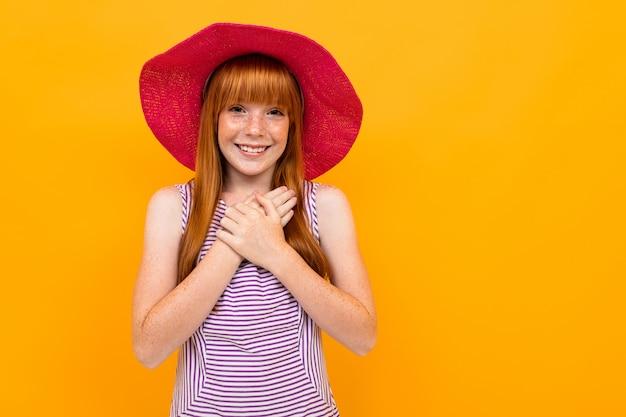 赤い髪とピンクの帽子を持つ少女笑顔と黄色に分離された何かのための希望
