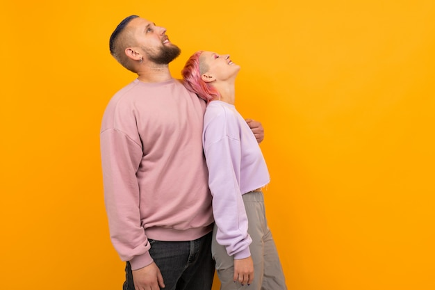 Необычная женщина с короткими розовыми волосами и татуировкой наслаждается жизнью со своим парнем на оранжевом