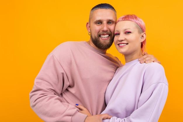 オレンジに分離された彼女のボーイフレンドと一緒に短いピンクの髪とタトゥーの異常な女性を抱擁します。