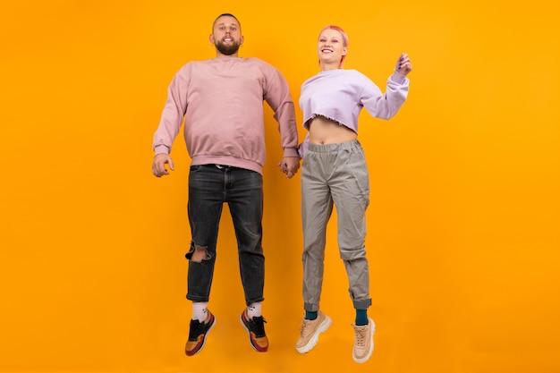 Необычная женщина с короткими розовыми волосами и татуировкой развлекается со своим парнем на оранжевом