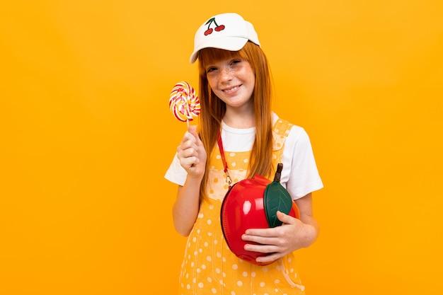 Девушка с рыжими волосами позирует на камеру с маленькой яблочной сумкой ест леденец, изолированный на желтом