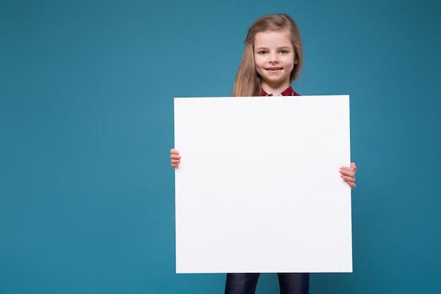 長い髪のシャツを着たかわいい女の子は、ホワイトペーパーを保持します。