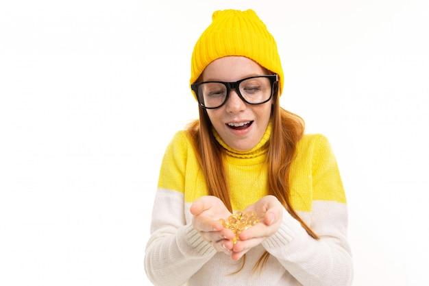 メガネで笑顔のヨーロッパの赤い髪の少女は白のレンズを保持します