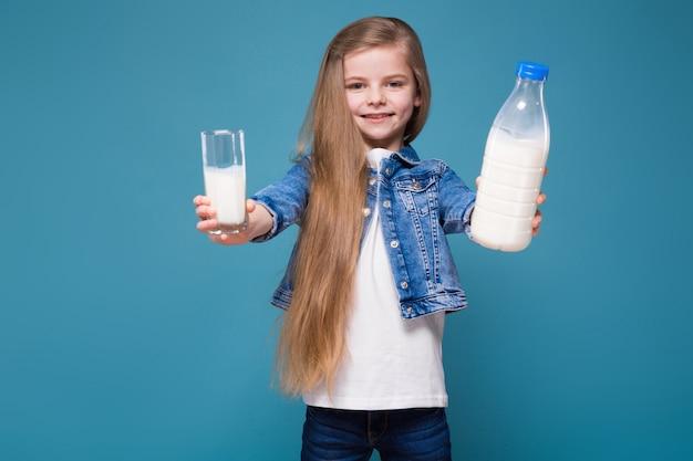 Маленькая красавица в джинсовой куртке с длинными каштановыми волосами держит контейнер для молока