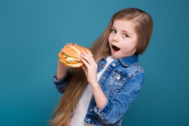 長い茶色の髪とジーンズのジャケットの小さなかわいい女の子はハンバーガーを保持します。