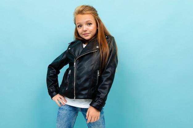 革のジャケットとジーンズでカジュアルな外観の女の子が水色に対して彼女の腰に手を置いた