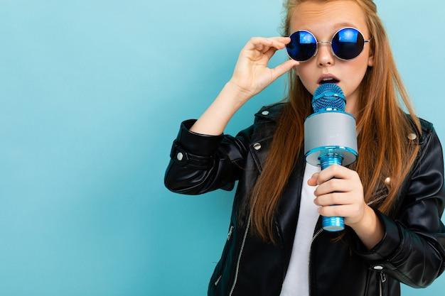 Удивленная европейская девушка в солнечных очках поет с микрофоном на голубом