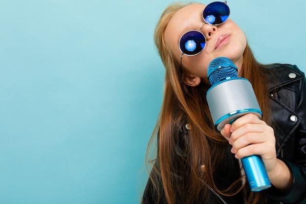 Портрет улыбающейся европейской девушки в темных очках поет с микрофоном на светло-голубой стене