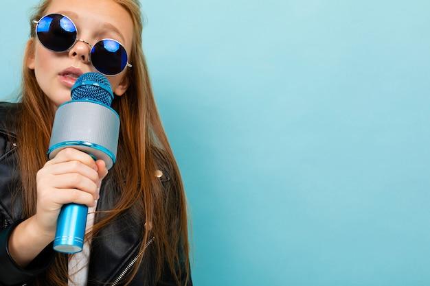 Европейская девушка в кожаной куртке в солнечных очках поет с микрофоном на голубом