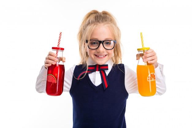 女の子は白い壁に飲み物を保持します