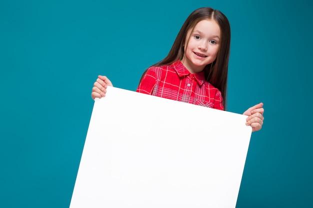 黒髪の市松模様のシャツでかわいい女の子はクリア紙を保持します。