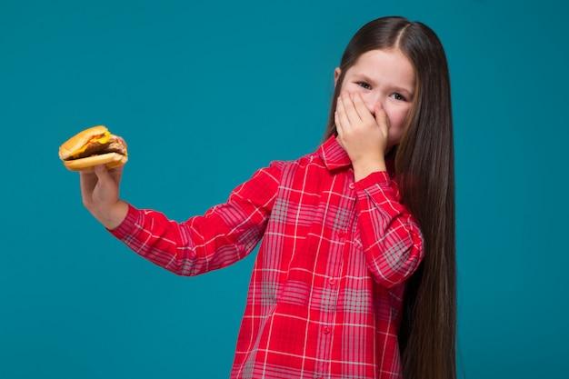 黒髪の市松模様のシャツでかわいい女の子はハンバーガーを保持