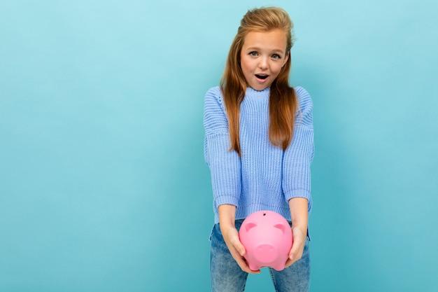 Красивая европейская девушка держит в руках копилку на светло-голубой