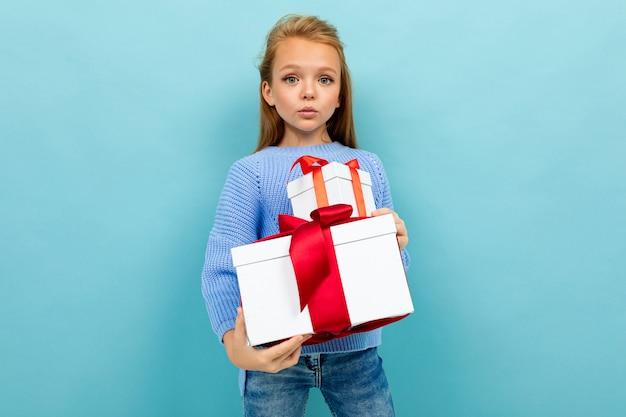 Маленькая кавказская девушка держит белые коробки с подарками и не имеет никаких эмоций, изолированных на синем
