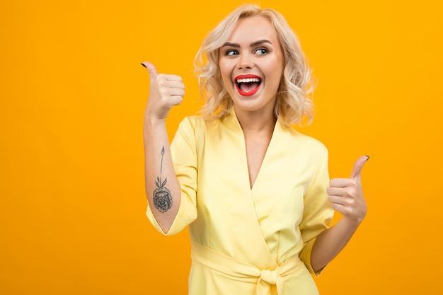 短いブロンドの髪を持つ陽気な若い女性は笑顔し、オレンジに分離された何かをお勧めします