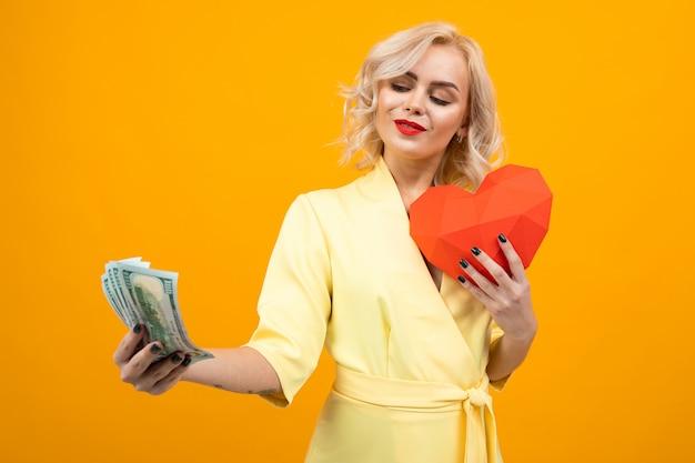 短いブロンドの髪を持つ陽気な若い女性は笑顔し、愛とオレンジに分離されたお金の間を選択します